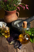 třecí miska s tloulem, láhve s olejovou a hliněnou vázu s čerstvými květinami na dřevěné ploše izolované na černém