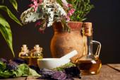 bílá Malta s pestlem v blízkosti lahví s olejem a vázy s čerstvými květy na dřevěném povrchu izolovanému na černém