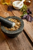 mortars with pestles with herbal mix near fresh basil on wooden surface