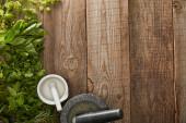 pohled na minomety s pestry v blízkosti čerstvé máty, bazalka a petržel na dřevěné ploše
