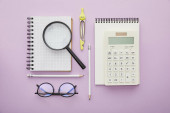 top view of magnifier on notebook near calculator and glasses isolated on purple