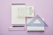 pohled shora na pravítkový trojúhelník na notebooku poblíž kalkulačky a šablony izolované na fialové