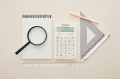 top view of magnifier on notebook near stationery isolated on beige