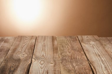empty wooden table on brown background with flashlight