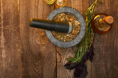 top view of mortar with pestle near fresh herbs and bottles on wooden surface with copy space