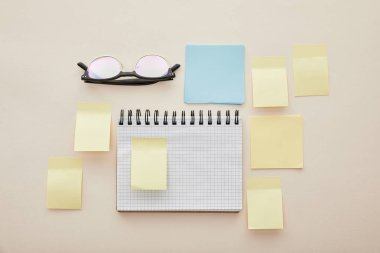 Top view of blank sticky notes on notebook near glasses isolated on beige stock vector