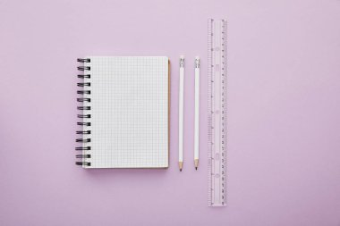 Top view of notebook near pencils and ruler isolated on purple stock vector