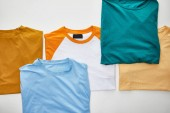 top view of beige, orange, blue, turquoise and ochre folded t-shirts on white background