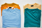 top view of beige, orange, blue, turquoise and ochre t-shirts on white background