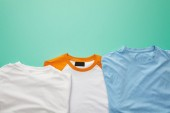 top view of folded plaid color t-shirts on turquoise background