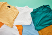 top view of folded orange, beige, white, blue and ochre t-shirts on turquoise background
