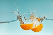 fresh orange halves falling in water with splashes on blue background