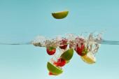 reife Limettenstücke und Erdbeeren, die tief ins Wasser fallen, mit Spritzer auf blauem Hintergrund