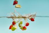 vápenné kousky a jahody hluboko ve vodě s šplouchnutím na modrém pozadí