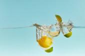 reife Zitrone und geschnittene Limette tief ins Wasser fallen mit Spritzer auf blauem Hintergrund