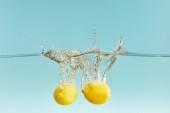 celé citrony, které jsou hluboko ve vodě s šplouchnutím na modrém pozadí