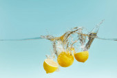 Photo fresh lemons falling deep in water with splash on blue background