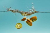 Photo kiwi slices falling deep in water with splash on blue background