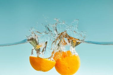 Ripe cut orange falling in water with splashes on blue background stock vector