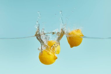Lemons falling deep in water with splash on blue background stock vector