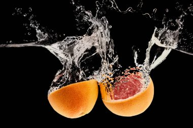 Ripe natural grapefruit halves falling in water with splash isolated on black stock vector