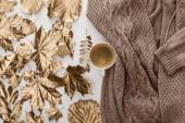 Draufsicht auf gestrickten braunen Pullover, Kaffee und goldenes Laub auf weißem Hintergrund