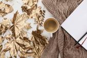 Draufsicht auf gestrickten braunen Pullover, Kaffee, leeres Notizbuch und goldenes Laub auf weißem Hintergrund