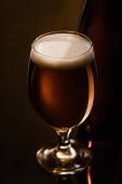 Fotografie blízký pohled na pivo s bílou pěnou ve skle na tmavém pozadí s osvětlením