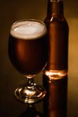 selektivní zaměření piva s pěnou ve skle blízko láhve na tmavém pozadí s osvětlením