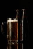 pohár sör hab közeli vizes palackok izolált fekete