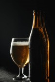 vlhké láhve piva s kapkami v blízkosti skla s pivem a pěnou, izolované na černém
