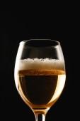 sklenice piva s pěnou izolovanou na černém
