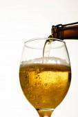 vista ad angolo basso della birra versando dalla bottiglia in vetro isolato su bianco