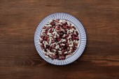 top view of striped plate with raw beans on wooden table