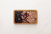 top view of rectangular wooden dish with raw beans on white marble surface