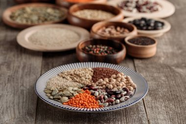 wooden and ceramic plates with legumes and cereals on brown table