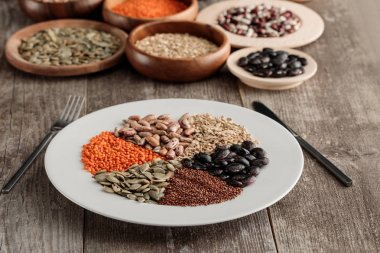 white plate with raw lentil, beans, pumpkin seeds, quinoa and oatmeal with knife and fork on wooden table