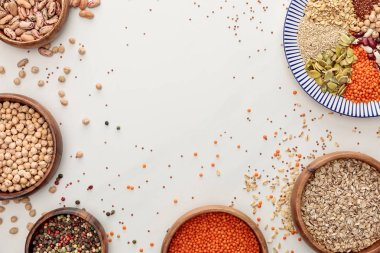 top view of plate and bowls with raw lentil, quinoa, oatmeal, beans, peppercorns and pumpkin seeds on marble surface with scattered grains and copy space