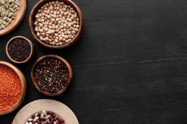 Top view of black quinoa, red lentil, beans, pumpkin seeds, peppercorns and chickpea on dark wooden surface stock vector