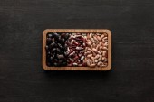 top view of rectangular brown bowl with raw assorted beans on dark wooden surface with copy space