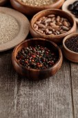 small wooden bowls with peppercorns, seeds and beans on brown table