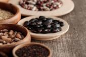 Braune Schalen und Teller mit schwarzen Bohnen und Körnern auf dem Tisch