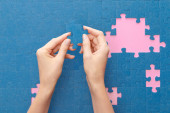 cropped view of woman holding blue jigsaw puzzle on pink background