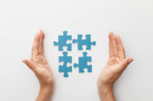 cropped view of woman hands near pieces of blue jigsaw puzzle on white background