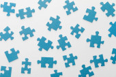 Photo top view of scattered blue jigsaw puzzle on white background