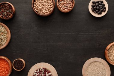 top view of legumes and cereals in bowls on dark wooden surface with copy space