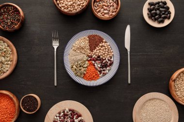 top view of knife and fork near striped plate with various raw legumes and cereals and bowls on dark wooden surface