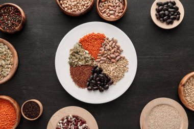 top view of white plate with various raw legumes and cereals near bowls on dark wooden surface