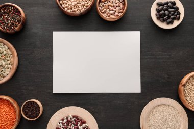 blank white paper on dark wooden surface with bowls with cereals and legumes