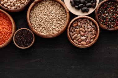 top view of raw beans, cereals and spice in bowls on dark wooden surface with copy space